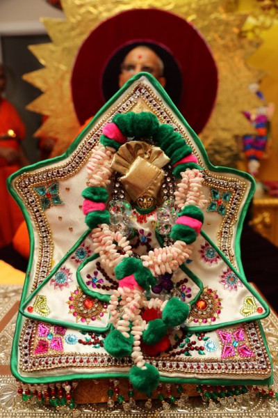 Divine darshan of Shree Harikrushna Maharaj adorned in a garland with individually-strung pieces of puffed rice, each with �Swaminarayan� written on them