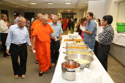 Acharya Swamishree consecrates the evening�s mahaprasad and blesses the Kitchen Committee volunteers