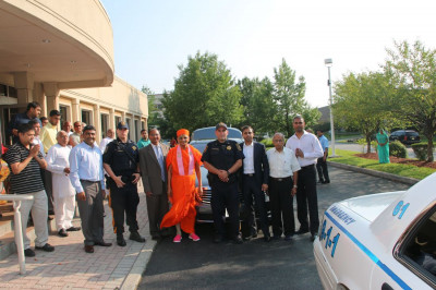 Acharya Swamishree, police officers, and disciples before Acharya Swamishree departs the temple for the airport