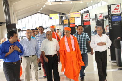 Acharya Swamishree walks through the airport terminal with disciples