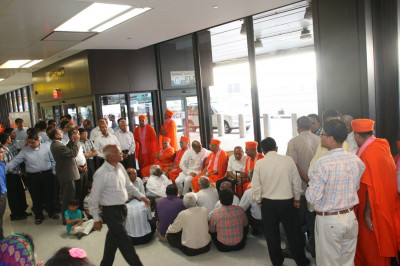 Disciples have the darshan of Acharya Swamishree in the airport terminal before He heads towards security