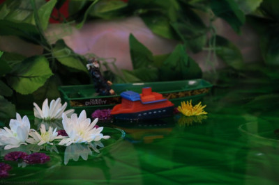 Flowers and boats floating on water as part of annakut decoration