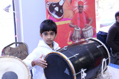 A young open house guest attempts to play the dhol