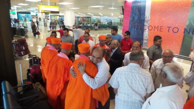 Disciples embrace sants shortly after they land at Newark Liberty International Airport