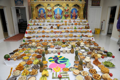 An annakut of various foods, sweets, and fruits is offered to Lord Swaminarayan