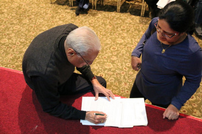 A temple volunteer helps a patient complete her health form