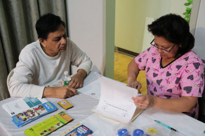 A nurse reviews the health camp results with a patient