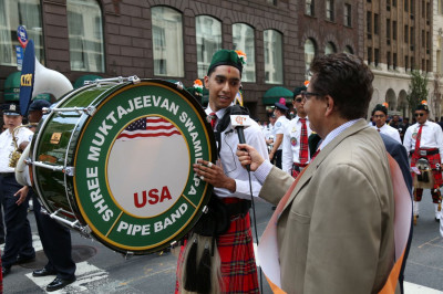 A Shree Muktajeevan Swamibapa Pipe Band USA member is interviewed by a reporter