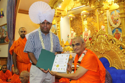 A guest presents an award to Acharya Swamishree for the temple on the 2nd anniversary