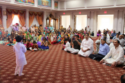 The congregation carefully listens as a young disciple delivers a speech about Acharya Swamishree