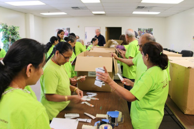Volunteers sort through thousands of syringes and package them by size that will be ready to be shipped out