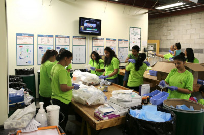 Volunteers sort through and package medical needles that will also be ready to be shipped out on the next shipment