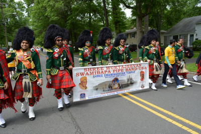 Shree Muktajeevan Swamibapa Pipe Band USA walks through the NJ Sharing Network 5k holding the Shree Swaminarayan Temple banner