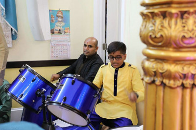 Disciples play various percussion instruments to provide live music for the samuh raas