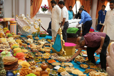 Disciples organize the annakut of various sweets, savory snacks, international dishes, tropical juices, and fresh fruits