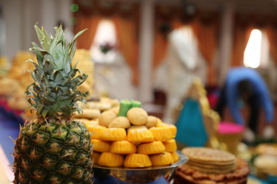 Fresh fruits, such as pineapples, and Indian delicacies, such as penda, are offered as part of the annakut for Lord Shree Swaminarayanbapa Swamibapa