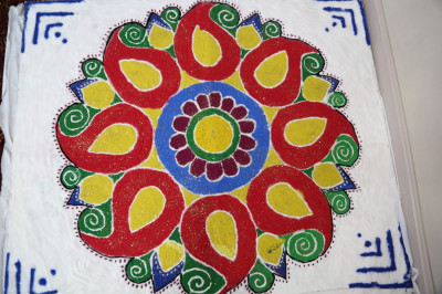 Decorative colored sand rangoli designs were made to place around the annakut