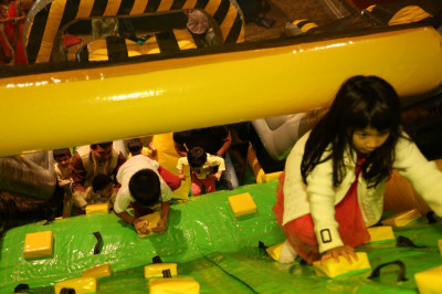 Young children enjoy the various activities offered during the open house, such as the obstacle course