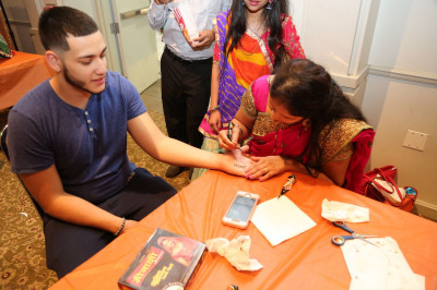 A college student experiences Hindu culture firsthand by getting a sample of mehndi (henna)
