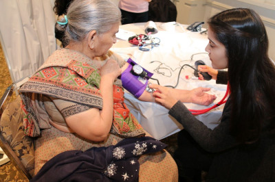 A patient has her blood pressure checked by a volunteer physician