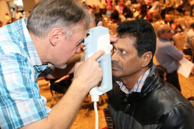 A patient has his pupils checked by physician volunteers from Project BEST