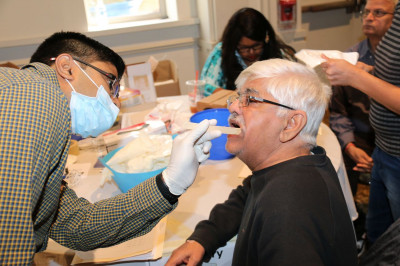 A patient has his teeth checked by a volunteer dentist