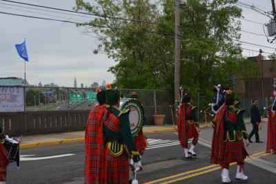 Shree Muktajeevan Swamibapa Pipe Band USA marches on Patterson Plank Road with the New York City skyline in the distance
