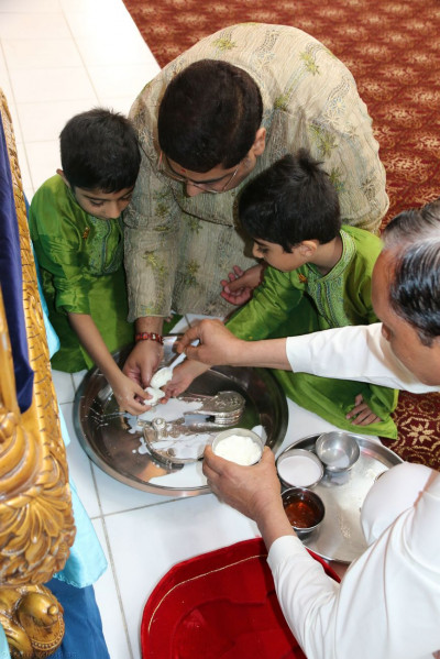 Disciples cleanse Lord Shree Swaminarayan�s lotus feet with milk, honey, sugar, yogurt, and saffron