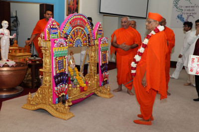 Acharya Swamishree examines the hindola decorations made from various candy bars