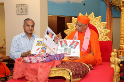 A disciple presents Acharya Swamishree with a scrapbook filled with birthday cards  made by the disciples of the temple