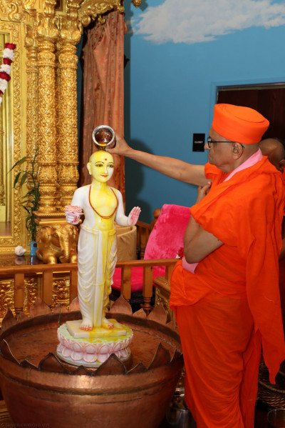 Acharya Swamishree bathes Lord Swaminaryanbapa Swamibapa in saffron water