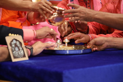 Acharya Swamishree and the main sponsors of the event perform panchamrut snaan to the divine lotus feet of Lord Shree Swaminarayan