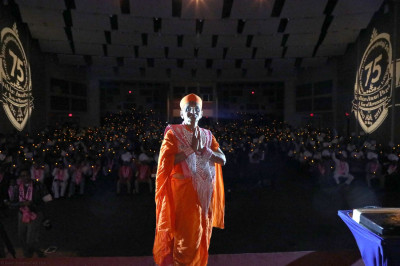 Divine darshan of Acharya Swamishree praying to Lord Shree Swaminaryan standing in front of a candle-lit congregation