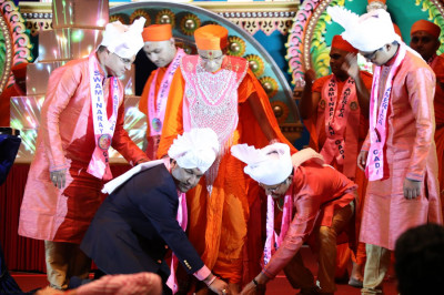 Acharya Swamishree blesses event sponsors as they adorn His divine lotus feet in chaakdi