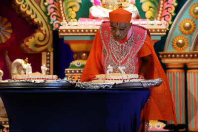 Acharya Swamishree blows the candles on the 75-pound birthday cake offered by Rajbhog Sweets, made entirely from Indian sweets