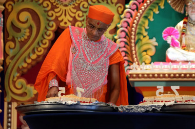 Acharya Swamishree cuts the the 75-pound birthday cake offered by Rajbhog Sweets, made entirely from Indian sweets