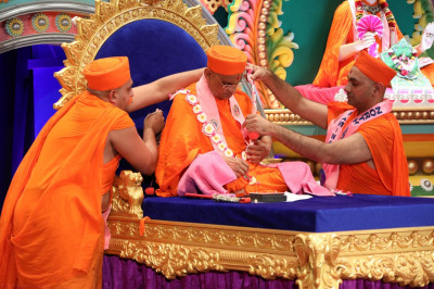 Sants adorn Acharya Swamishree in a garland made by disciples for the event