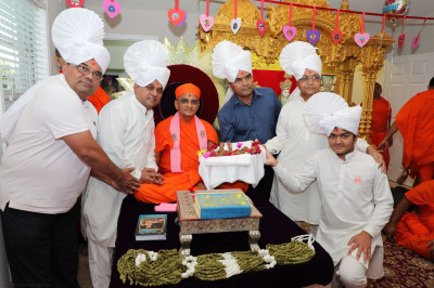 Disciples present Acharya Swamishree with garlands made from biscuits and pistachios