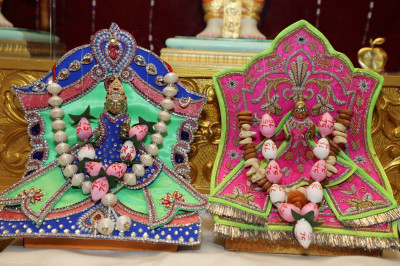 Divine darshan of Shree Harikrushna Maharaj adorned in flower bud garlands with '75' written on the petals