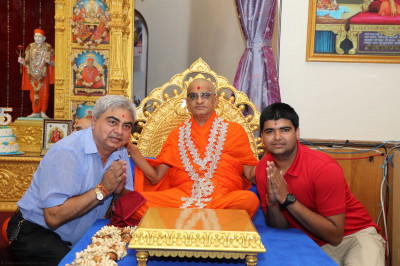 Acharya Swamishree blesses disciples who adorn Him in a special garland