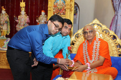Acharya Swamishree blesses disciples who offer a special rose to Him