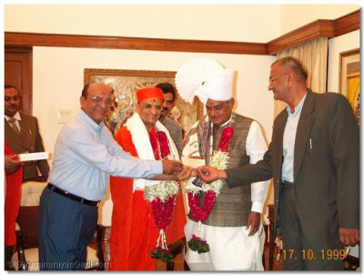 Acharya Swamishree and satsangis present Shree Bajpayeeji with a gift
