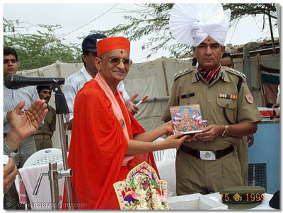 The Chief Commander being presented with the divine prasad of Lord Swaminarayan by Acharya Swamishree