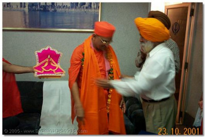 Shree Narendrapal Singh honours HDH Acharya Swamishree with a garland and shawl