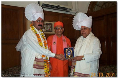 HDH Acharya Swamishree presents a momento to the hosts