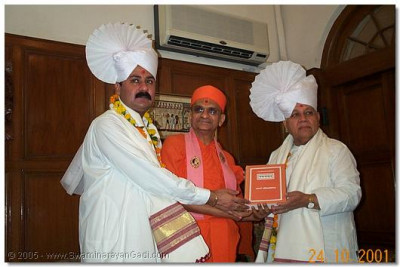 The hosts are presented with the Vachanamrut by HDH Acharya Swamishree