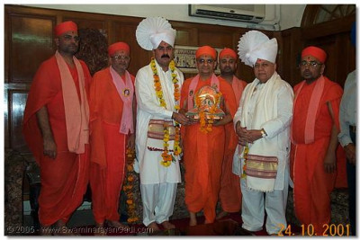 HDH Acharya Swamishree blesses the hosts with prasad paags and garlands