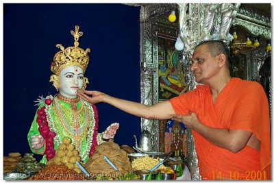 HDH Acharya Swamishree offering an item from the Thaal to Lord Swaminarayan