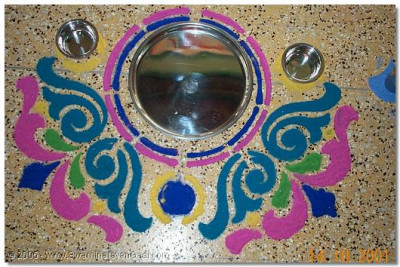 The completed rangoli within which are placed the plates and glasses for the sants