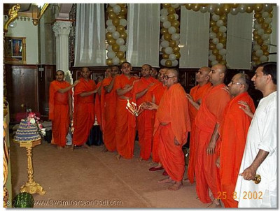 HDH Acharya Swamishree, sants and haribhakto doing aarti to Lord Swaminarayan, Jeevanpran Abjibapashree and Jeevanpran Swamibapa